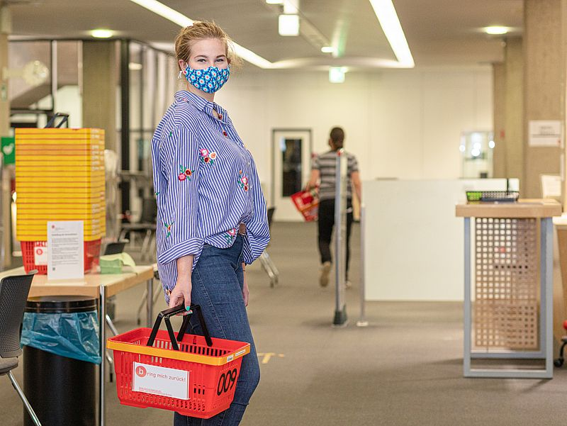 A student wearing a face mask in the library's entrance hall.