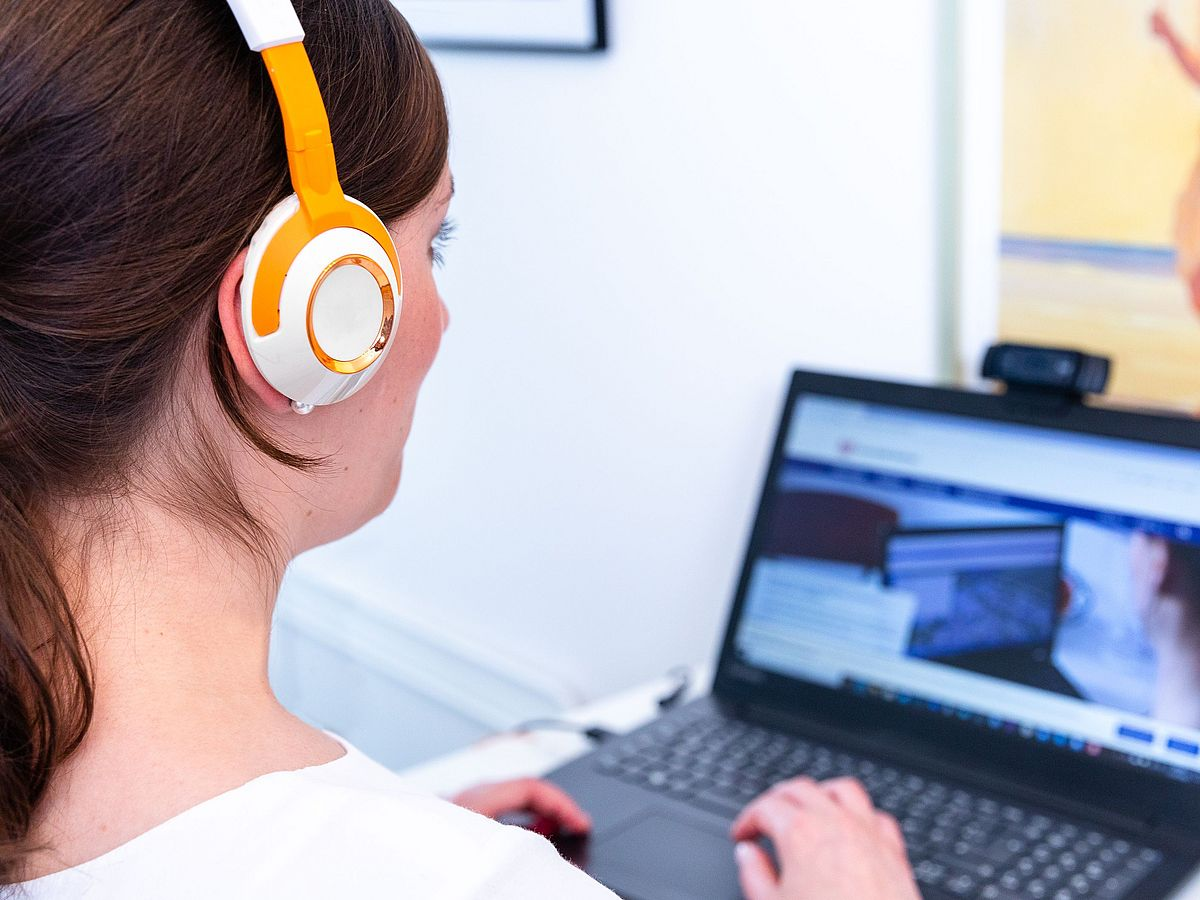 A person wearing headphones uses a laptop.