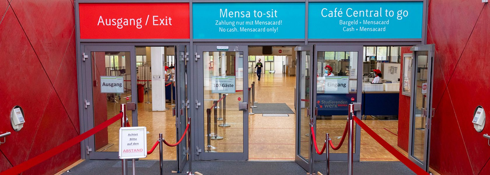 The entrance of the canteen on the campus of the University of Bremen: There are three doors, above each of them a lettering is attached: Exit, Mensa to sit and Café Central to go