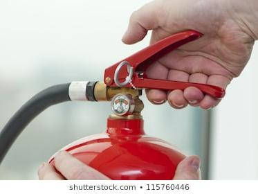 hand presses trigger of a portable fire extinguisher