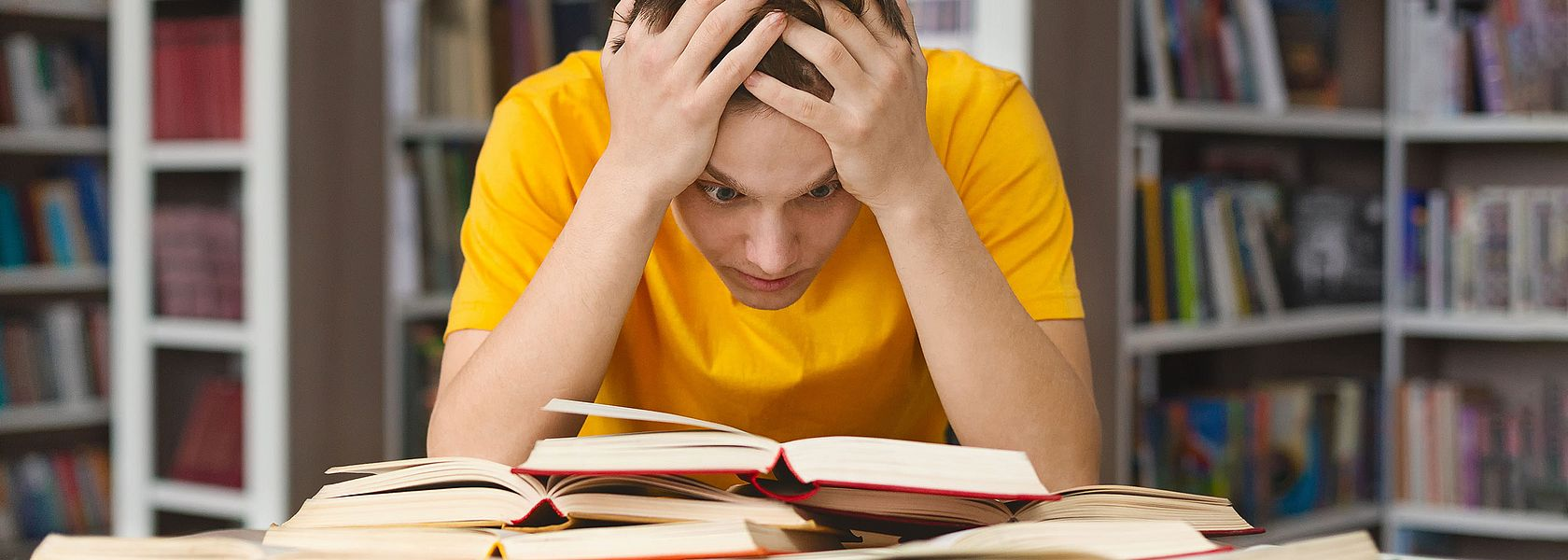 Boy with a yellow shirt leans over some books and looks desperate.