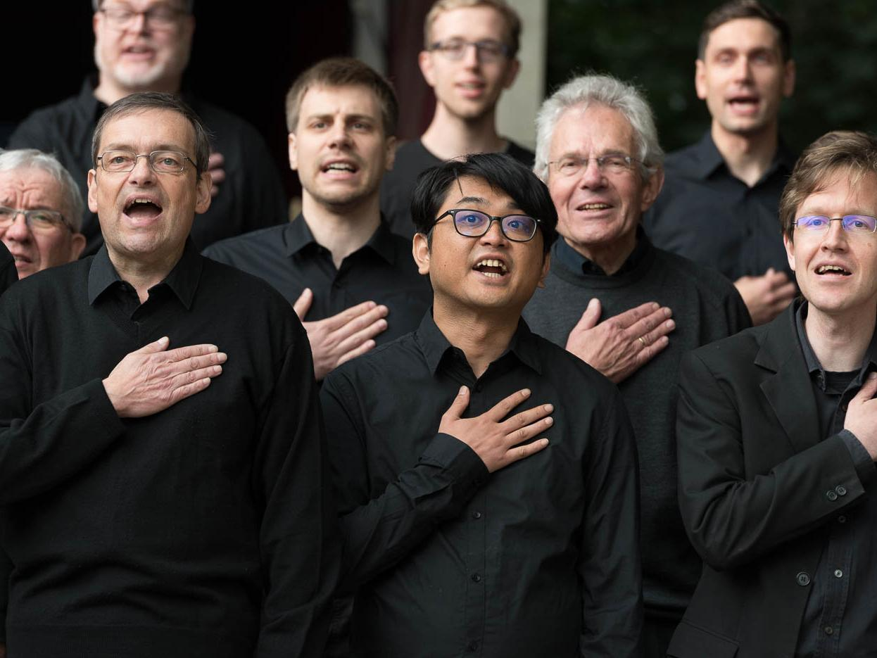 Male voices of the choir of Bremen University with the hand on the heart