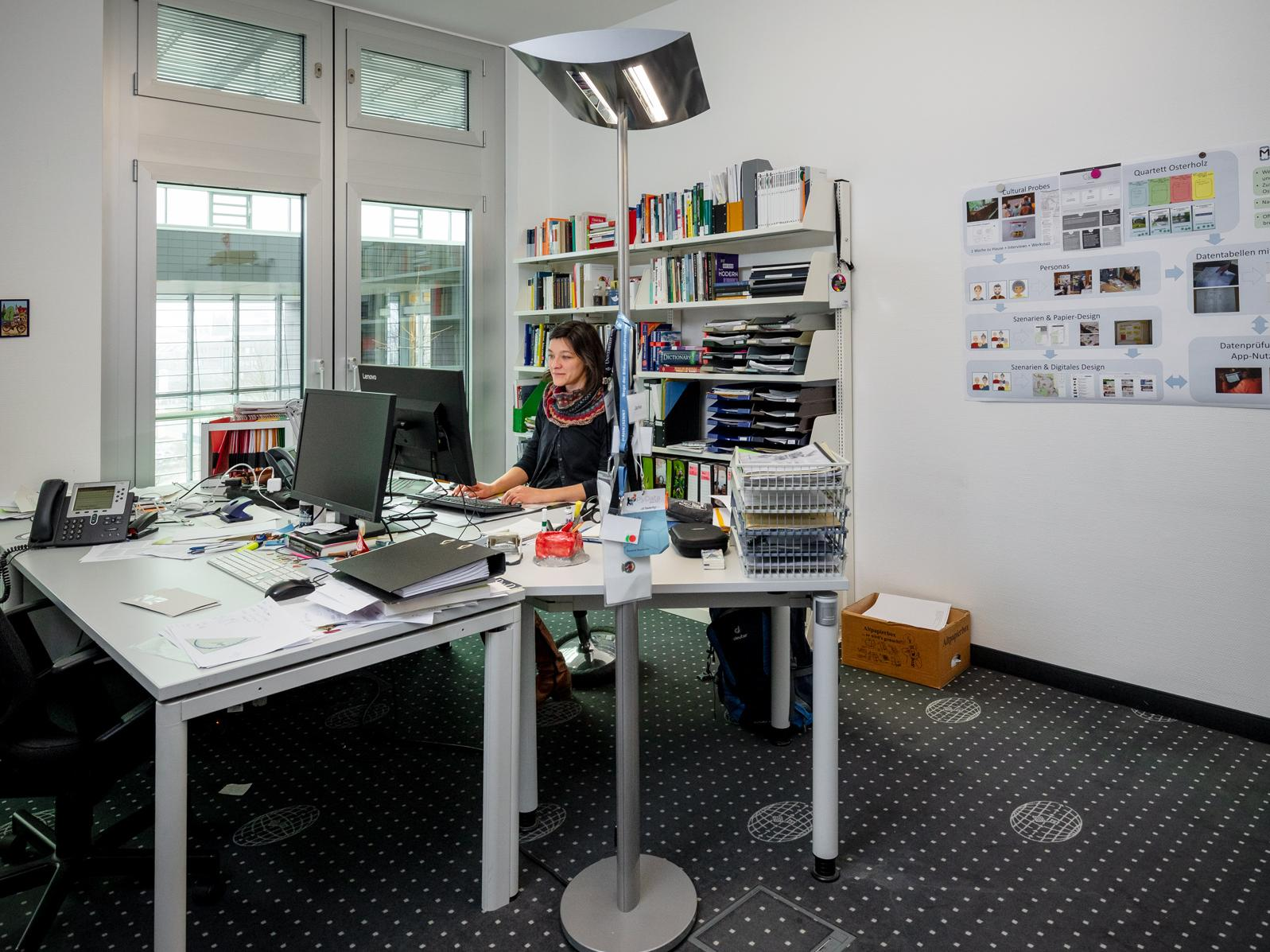 Dr. Juliane Jarke sits in her office at the desk and works.