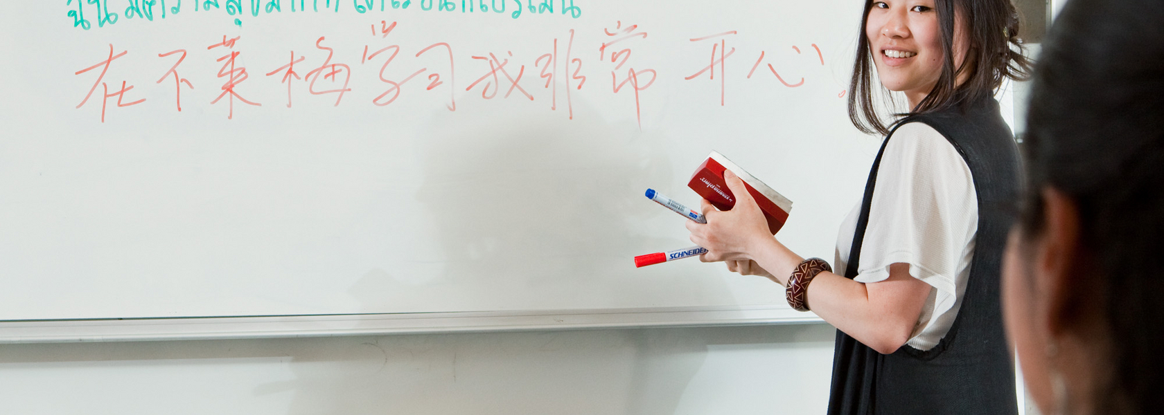 A person writes in different languages on a whiteboard.