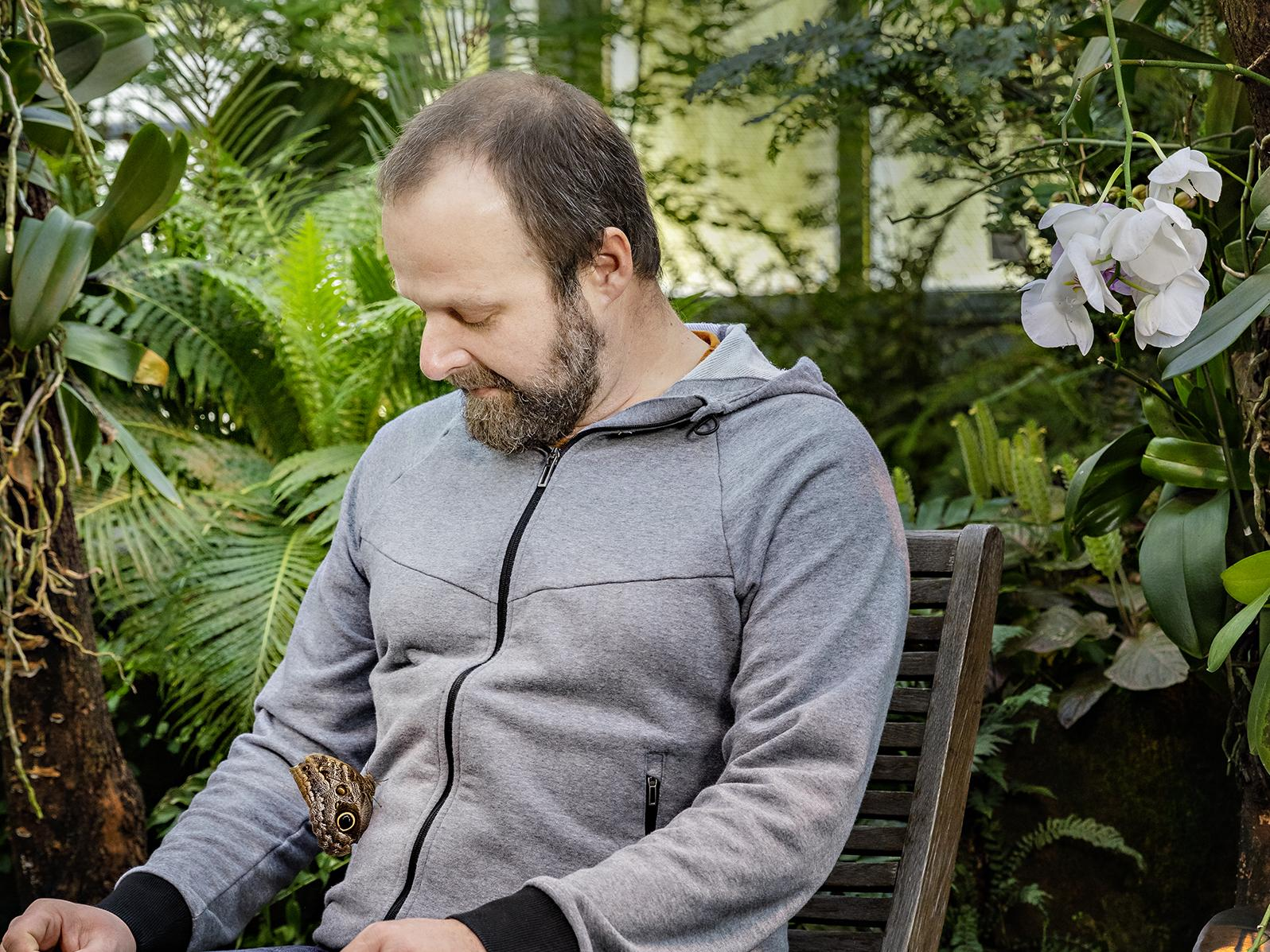 Thorsten Kluß in the Botanic Garden with a Butterflx on his knee.