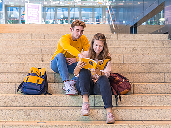 Young man and woman are sitting on stairs and are looking together in a book.