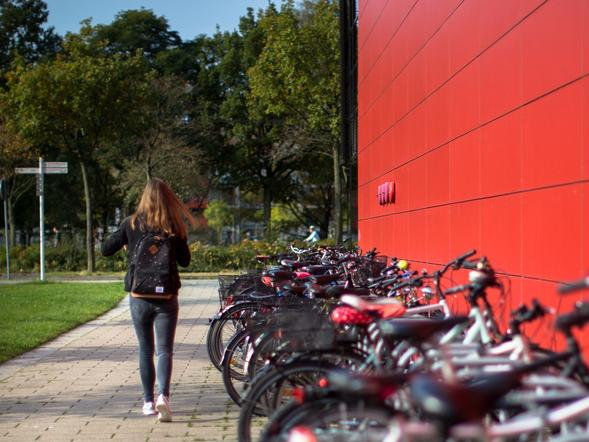 A girl walking by bicycles