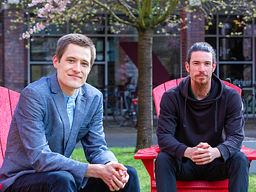 Two young men sit on red chairs in park and look at camera