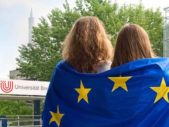 Two women with a European flag can be seen from behind