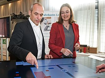Man and woman standing at digital table.