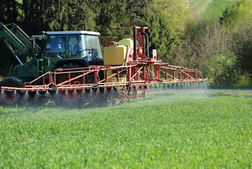 Tractor sprays pesticides in a field