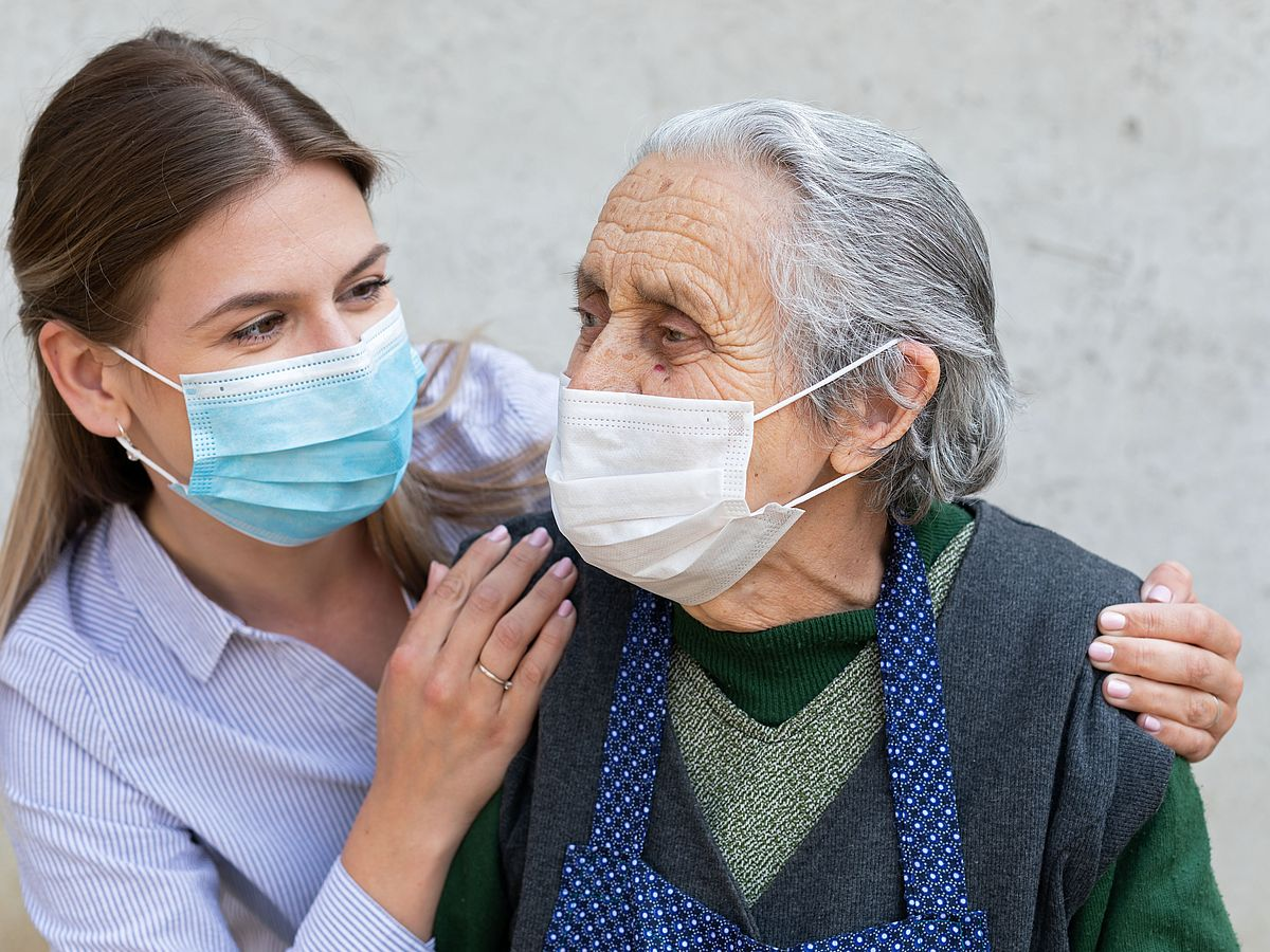 Nurse and resident of a nursing home with mouse-nose covering masks