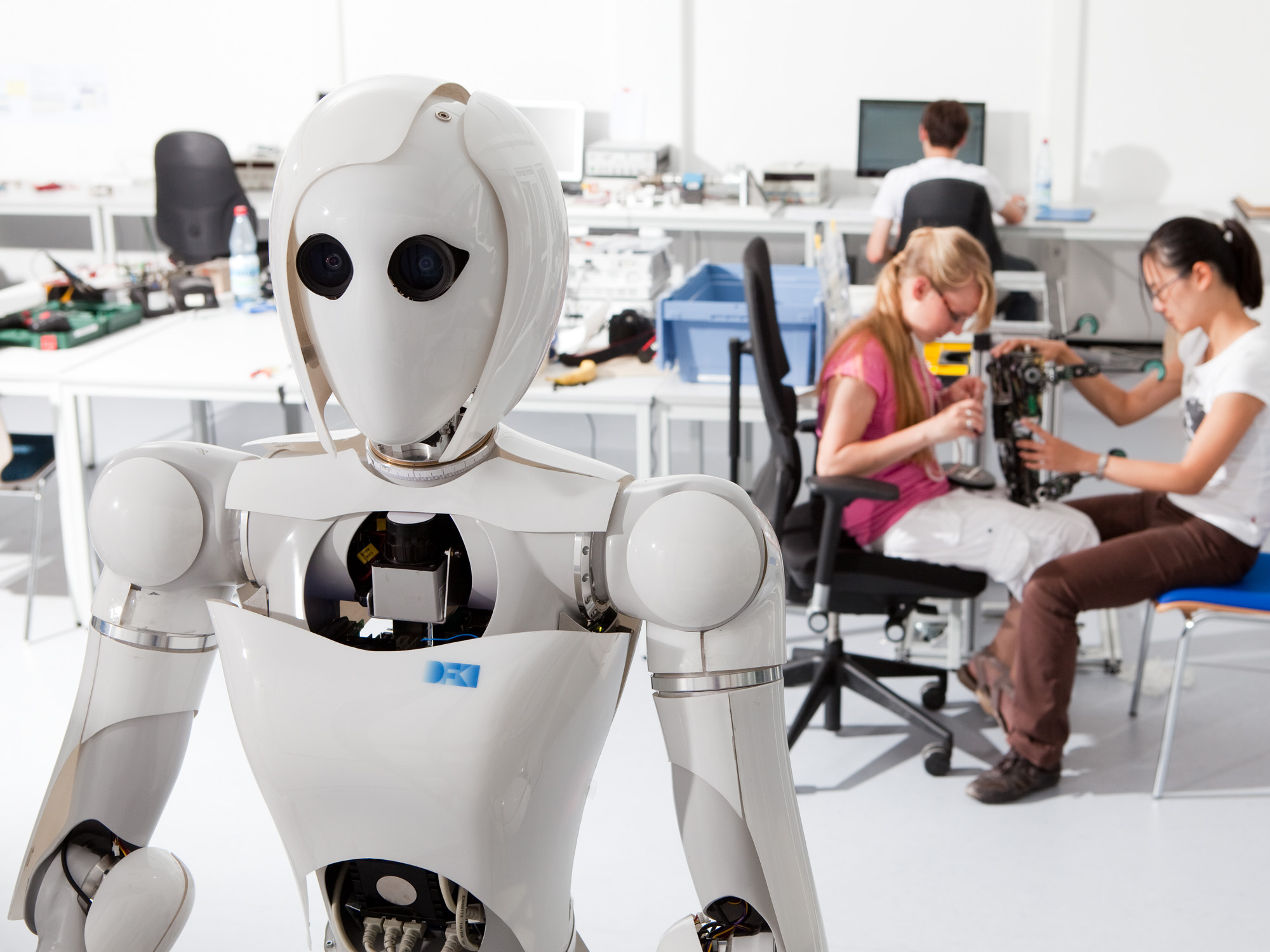 A humanoid robot in front of two people