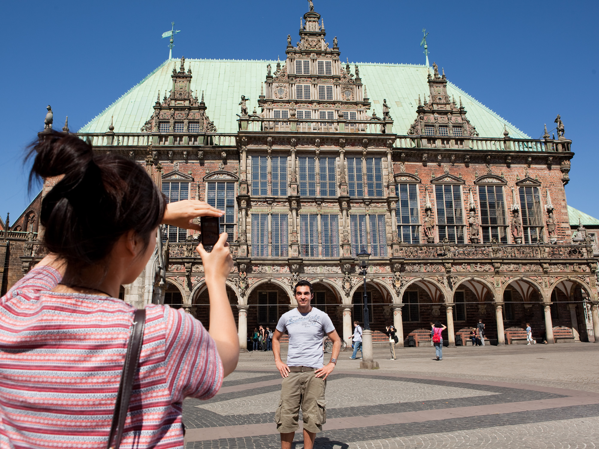 A woman, taking a photo of a man in front of the Bremer town hall