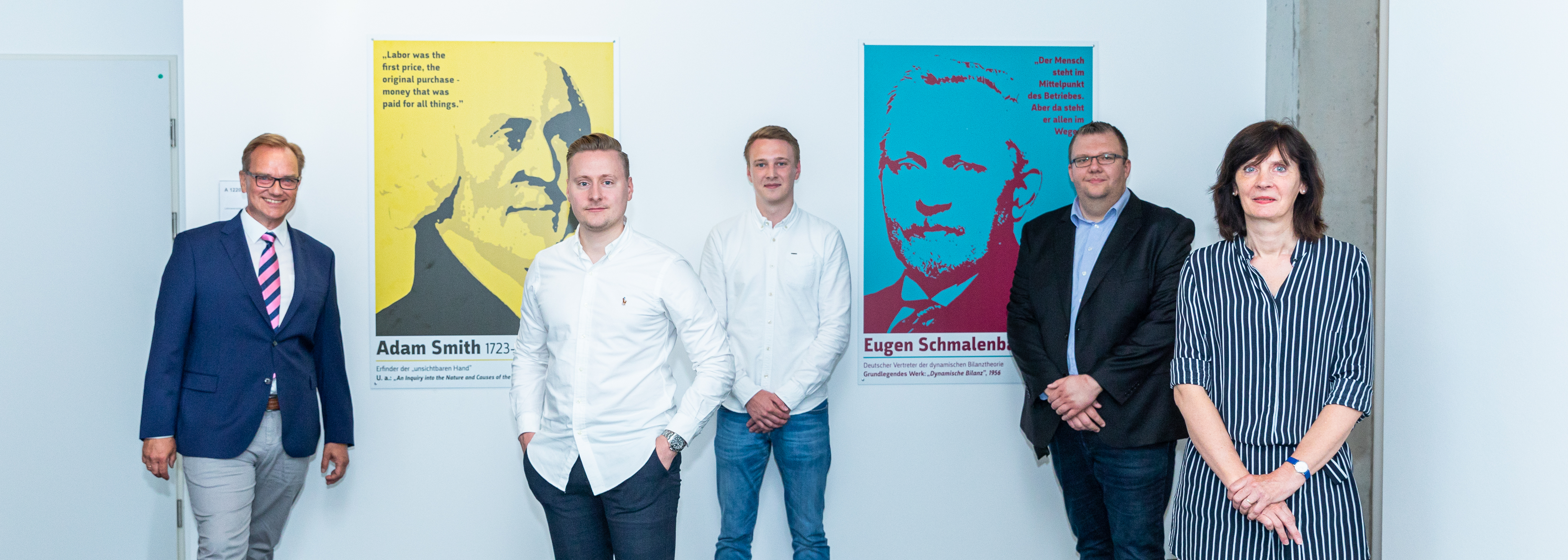 Five people stand in front of a wall with colourful posters.
